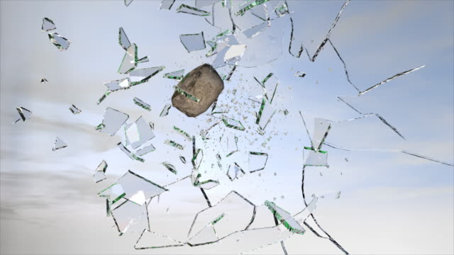 stone breaking glass during the day slow motion video