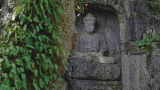 vídeos de stock, filmes e b-roll de estátua de buda de pedra na gruta do templo lingyin, hangzhou, china. - buda