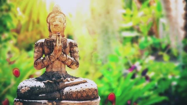 Stone Buddha Statue Stone Buddha Statue in green garden buddha stock videos & royalty-free footage