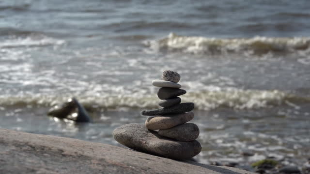 Stone cairn on the Baltic Sea with waves