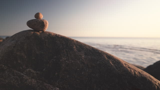 Stone cairn on the Baltic Sea with waves A pyramid of several stones on a large boulder against the background of the waves of the Baltic Sea in summer solid stock videos & royalty-free footage
