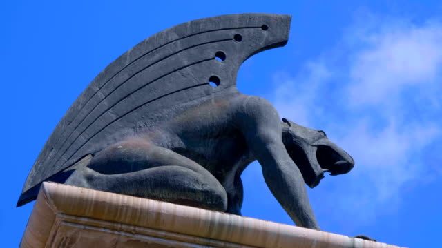 stone gargoyle with wings on a pedestal at the edge of the bridge over the river - mitologia video stock e b–roll