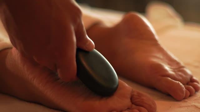 stone massage and spa therapy in luxury resort hotel. foot massage in spa salon. body relax and skin care concept. zen concept. antistress therapy in alternative medicine - terapia lastone filmów i materiałów b-roll