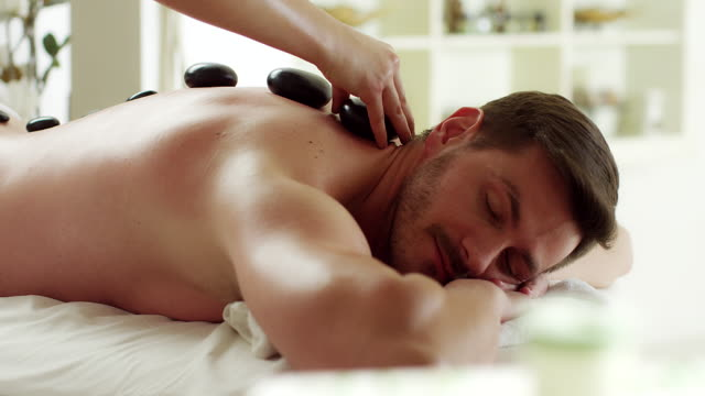 Stone massage Man having stone massage in spa salon. Video. spa treatment stock videos & royalty-free footage