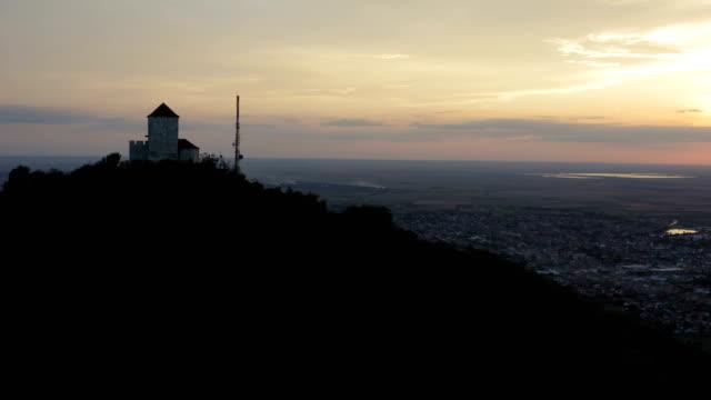 gün batımında bir dağın tepesinde bir taş ortaçağ kulesi - sale stok videoları ve detay görüntü çekimi