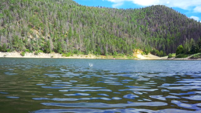 Stone Skips Across Surface of Mountain Lake video