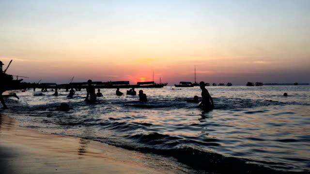 gün batımı sırasında stone town plaj aktivitesi - kültürler stok videoları ve detay görüntü çekimi