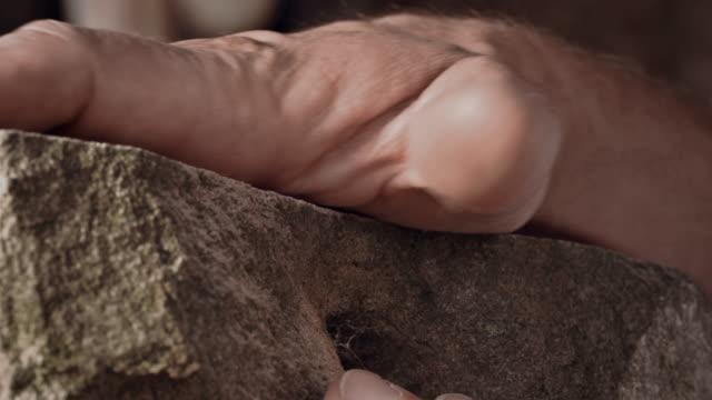vídeos de stock e filmes b-roll de stonemason caressing stone - material de construção