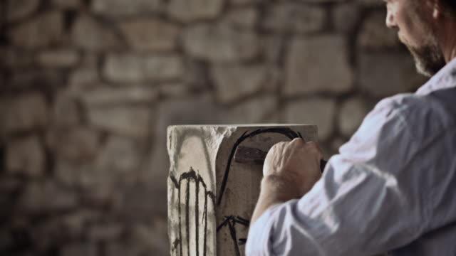 stonemason carving pietra con martello e scalpello - incisione oggetto creato dall'uomo video stock e b–roll