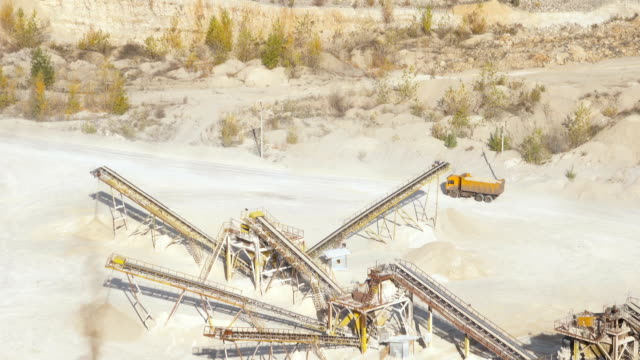 Stones crushing and gravel production on mining quarry. Raw mining materials moving along an exterior conveyor belt