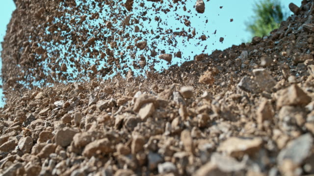 SLO MO Stones falling on a pile in sunshine