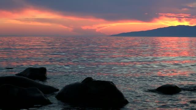 vídeos de stock e filmes b-roll de stones in water on sunset background - lago baikal