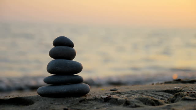 Stones on the beach at sunset Stacked stones on the beach at sunset boulder rock stock videos & royalty-free footage