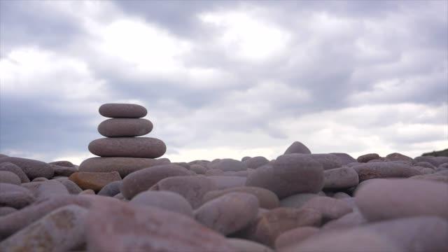 stenar pyramid på stenstrand, symboliserar harmoni, balans, zen, motion - sten konstruktionsmaterial bildbanksvideor och videomaterial från bakom kulisserna
