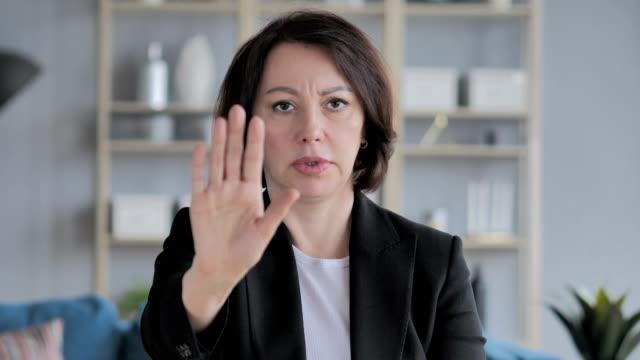 stop gesture by old businesswoman, denying offer - negacja filmów i materiałów b-roll