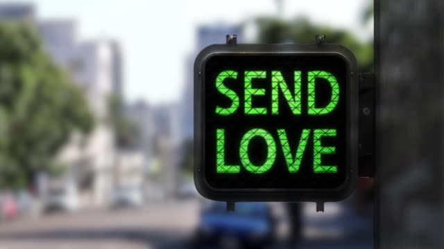 Stop Hate. Send Love—Medium shot of Walk Signal with hopeful social message