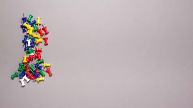 Stop motion animation of colorful push pins on gray background with copy space