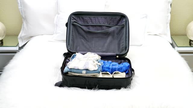 4 k は、女性の服でいっぱいにされている空のスーツケースのモーション アニメーションを停止します。 - 荷造り点の映像素材/bロール
