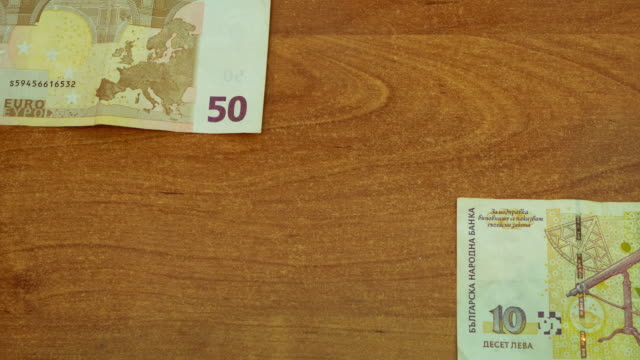stop motion animation of euros and lev on wooden desk stop motion animation of 50 euros and 10 Bulgarian lev on wooden desk. banknotes moving from different sides, meet at middle for a second and then moving out of sight. looped closeup 4k video schengen agreement stock videos & royalty-free footage