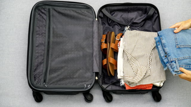 4K stop motion animation of female hands packing clothes into a suitcase