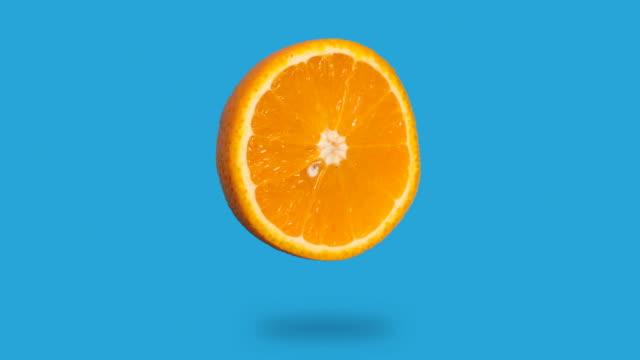 신선한 오렌지 주스의 중지 모션 애니메이션이 사라지고 파란색 배경에 나타납니다. - 주황색 스톡 비디오 및 b-롤 화면