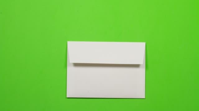 stoppa rörelseanimering av gult pappersveck och hamnar i ett vitt kuvert. lämnar sedan skärmen till höger - kuvert bildbanksvideor och videomaterial från bakom kulisserna