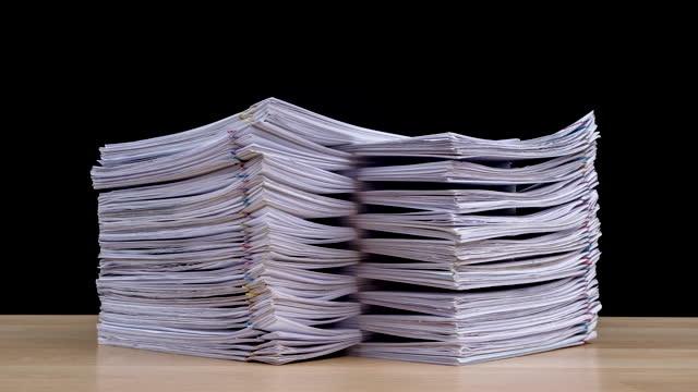 animazione in stop motion stack sovraccarica i file cartacei dei documenti sulla scrivania dell'ufficio isolata su sfondo nero, concetto business. - catasta video stock e b–roll