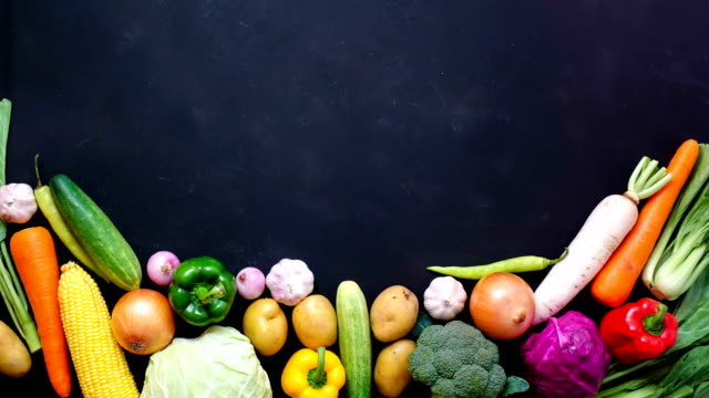 Stop motion animation top view vegetables and pan on black color background for copy space video