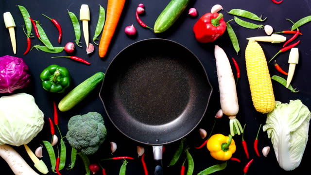 stop motion animation top view vegetables and pan on black color background - cibi e bevande video stock e b–roll