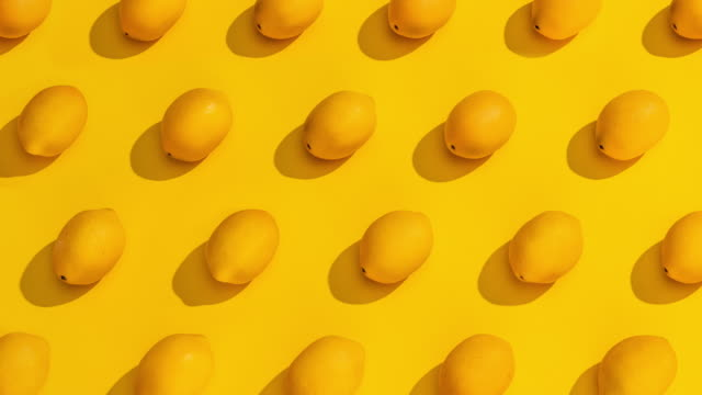stop motion collection of lemons on a yellow background. - лимон стоковые видео и кадры b-roll