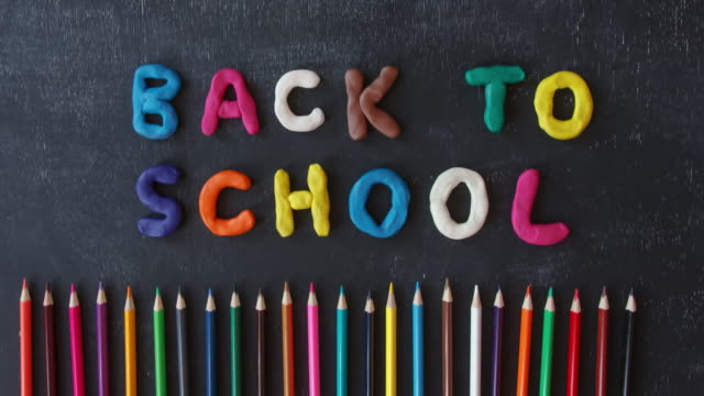 Stop motion hand made plasticine lettering back to school on the blackboard. Fun cartoon rainbow modeling clay. Colored pencils. video
