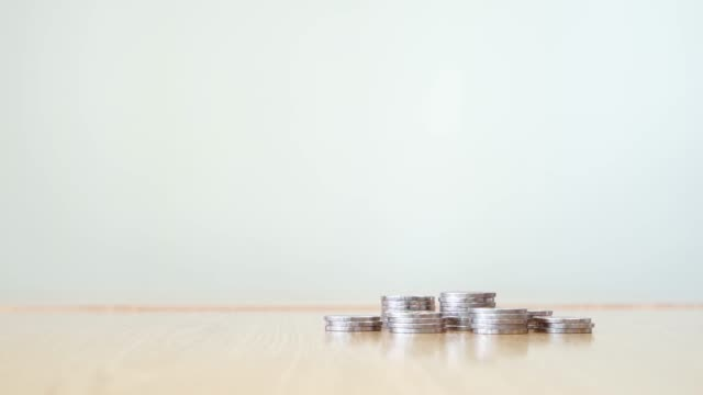 Stop motion increasing pile of silver coins on wooden table at right corner with white color background