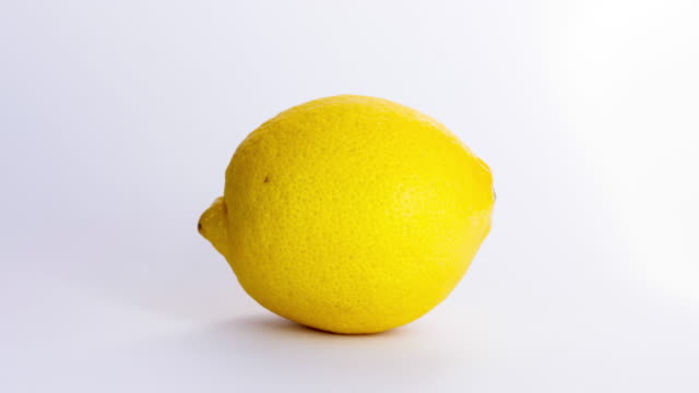 stop motion lemon rotating isolated on a white background. seamless loop 4k movie. - лимон стоковые видео и кадры b-roll