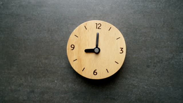 stop motion of a vintage small wooden clock with the time passing on the black table - время дня стоковые видео и кадры b-roll