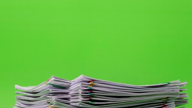 4k stop motion della carta di report del documento di sovraccarico dello stack ravvicinato con il posto della graffetta aumenta e diminuisce su sfondo verde, filmati concettuali aziendali e educativi senza carta utilizzati. - catasta video stock e b–roll
