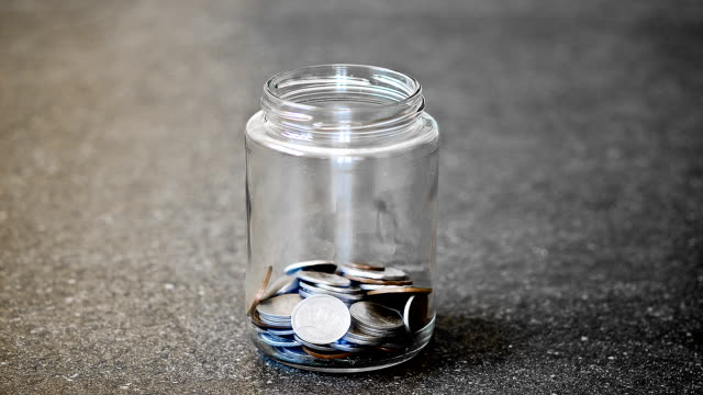 Stop motion of glass jar filled with coins video