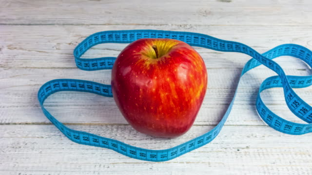 Stop motion of the measuring tape wrapped around the red apple. Timepalse of healthy lifestyle diet concept video