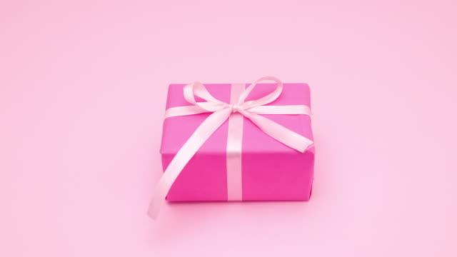 vídeos de stock, filmes e b-roll de pare o movimento de amarração de fita rosa no presente - presente