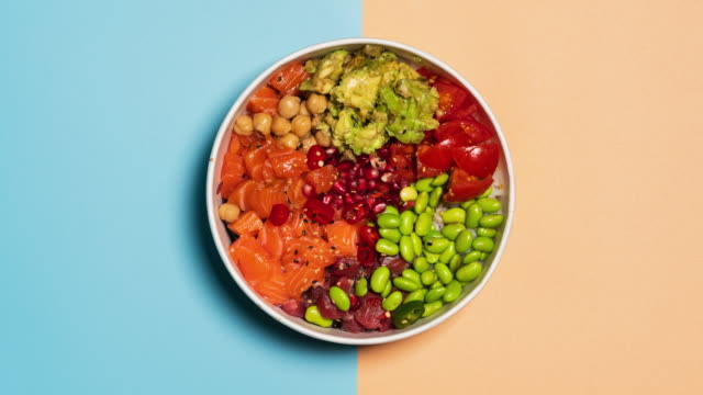 vídeos de stock e filmes b-roll de stop motion video of an hawaiian poke bowl with rice, salmon, avocado, tomatoes, tuna, chickpeas, pomegranate and edamame. top view from above. - vegetables