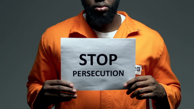 Stop persecution phrase on cardboard in hands of Afro-American prisoner, assault Stop persecution phrase on cardboard in hands of Afro-American prisoner, assault civil rights stock videos & royalty-free footage