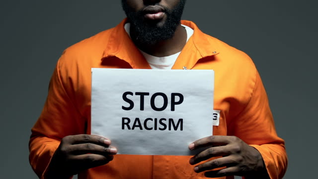 Stop racism phrase on cardboard in hands of black prisoner, discrimination Stop racism phrase on cardboard in hands of black prisoner, discrimination civil rights stock videos & royalty-free footage