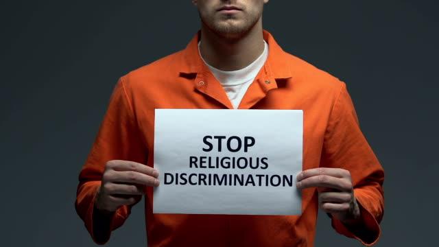 stop religijnej dyskryminacji wyrażenie na karcie w rękach kaukaskiego więźnia - zwrot filmów i materiałów b-roll