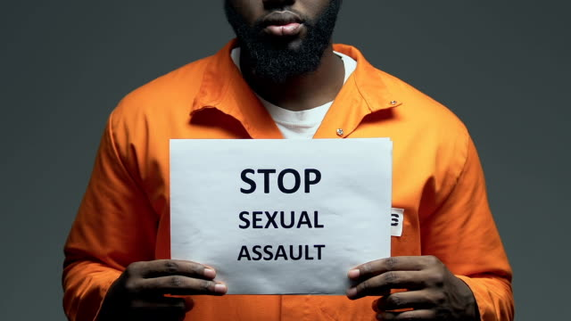 Stop sexual assault phrase on cardboard in hands of black prisoner, raping Stop sexual assault phrase on cardboard in hands of black prisoner, raping civil rights stock videos & royalty-free footage