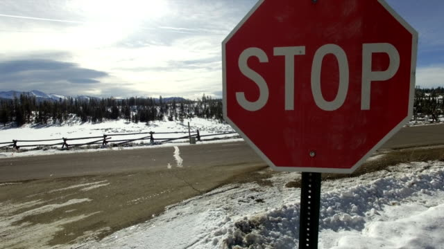 Stop sign on snowy mountain road video