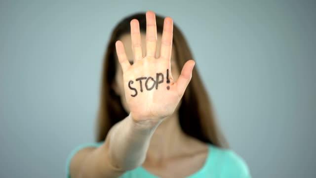 vídeos y material grabado en eventos de stock de señal de stop en la mujer de las manos, protección de los derechos femeninos, conciencia del problema - stop sign