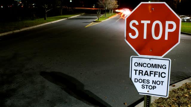 vídeos y material grabado en eventos de stock de señal de pare (stop) con luces borrosas timelapse noche - stop sign