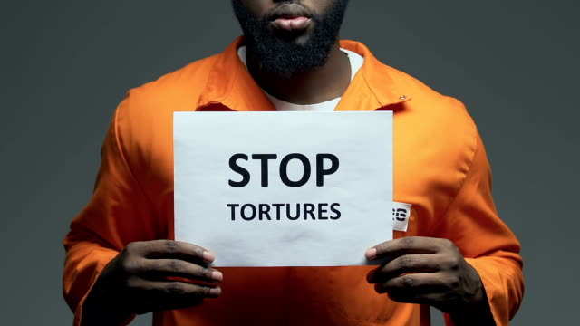 Stop tortures phrase on cardboard in hands of Afro-American prisoner, assault Stop tortures phrase on cardboard in hands of Afro-American prisoner, assault civil rights stock videos & royalty-free footage