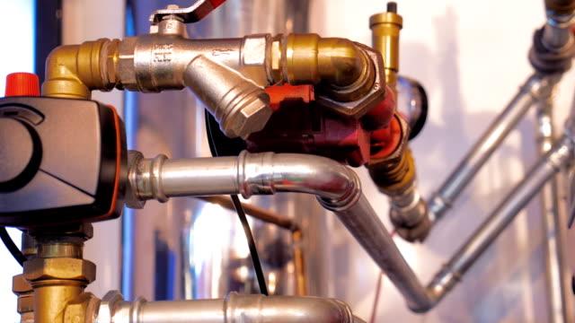 avstängningskranar, pipelines och kontrollenheter och reglera temperaturen på vattnet - värmepump bildbanksvideor och videomaterial från bakom kulisserna