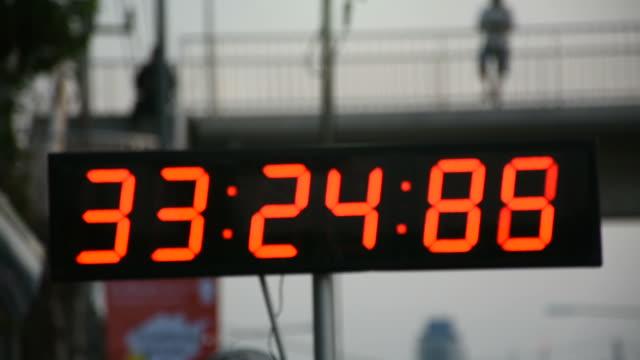 vidéos et rushes de chronomètre ou horloge numérique pour coureur de minuterie s'exécutant dans l'événement marathon course - chrono sport