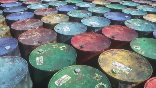 Storage of colorful rust metal barrels with toxic waste.